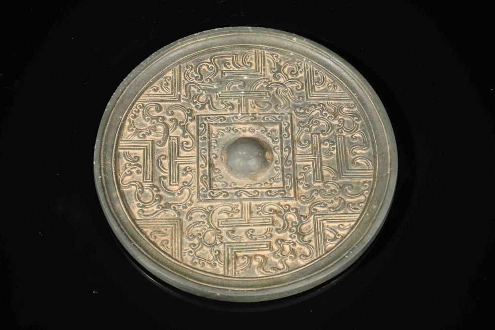 Miroir circulaire finement ciselé de rinceaux et motifs géométriques serti d'une bossette centrale de préhension .