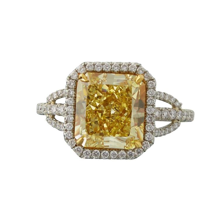 A fancy intense yellow diamond, platinum and eighteen karat gold ring,