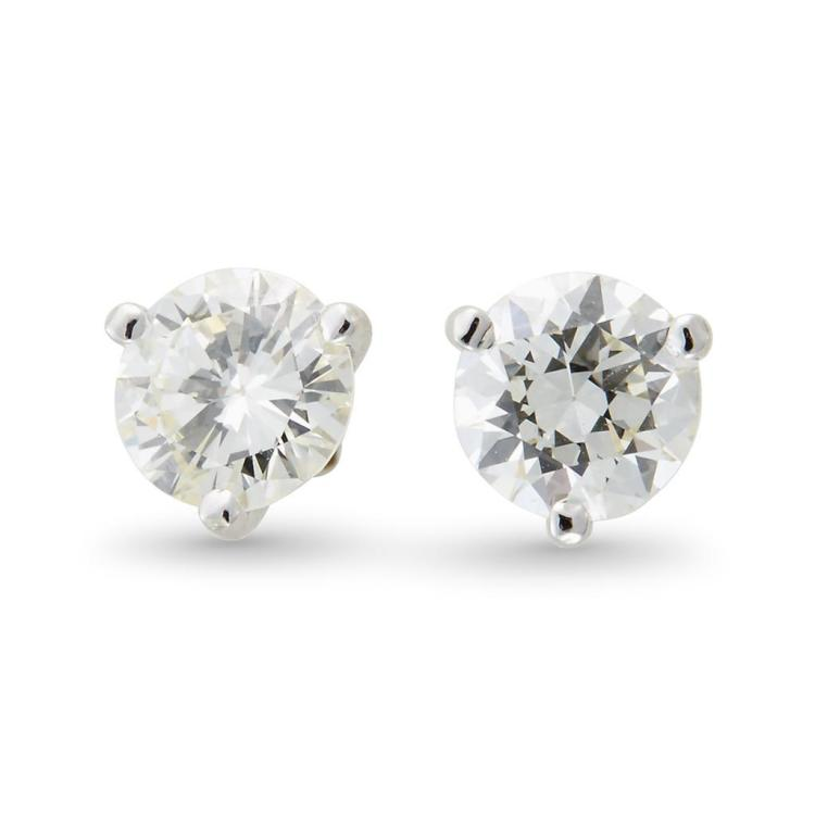A pair of diamond and fourteen karat white gold studs,