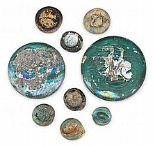 Nine Arabic iridesced glass tokens or Dirham weights, circa 11th-13th century, Comprising two large discs, and seven smaller with impre