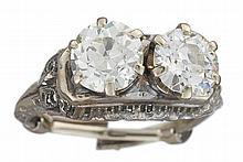 A diamond and platinum ring, circa 1900, set with two old European-cut diamonds, within a pierced foliate motif mount; diamonds estimat