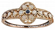 A diamond, sapphire, and fourteen karat rose gold bangle, , centering a round brilliant-cut sapphire, rose and table-cut diamonds, acce