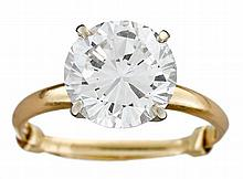 A diamond, platinum and eighteen karat gold solitaire ring, , set with a round brilliant-cut diamond approximately: 3.20 carats.