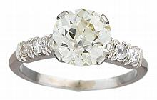 A diamond and platinum ring, , set with an old European-cut diamond, flanked by circular-cut diamonds; center diamond weighing approxim
