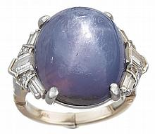 An Art Deco star sapphire, diamond and platinum ring, , centering a cabochon sapphire and accented by full, baguette and bullet-cut dia