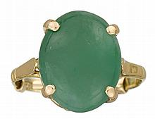 A jadeite and eighteen karat gold ring, , set with an oval cabochon jadeite, measuring: 12.00 x 15.09 x 8.48mm.