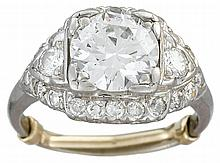 A diamond and platinum ring, , centering a transitional-cut diamond weighing approximately: 1.85 carats, accented by full and single-cu