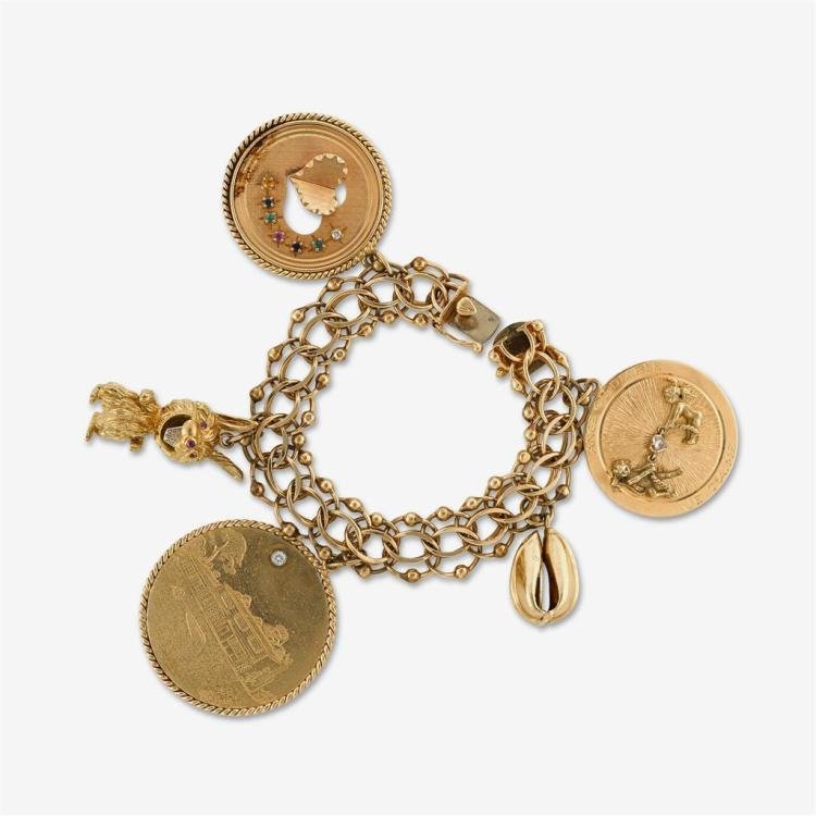A fourteen karat gold charm bracelet with five gem-set and gold charms,