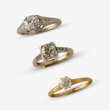A collection of three diamond and gold rings,