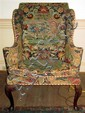 George II style mahogany wingback armchair, 19th century, Upholstered in eighteenth-century needlework, raised on short carved cabriole