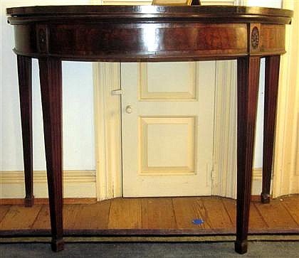 George III mahogany card table, circa 1780, The D-shaped foldover top over rosette carved apron, raised on fluted tapering legs termina
