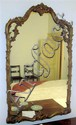 George III style giltwood mirror, 19th century, The shaped mirror plate within floral, C- and S-scroll carved frame.