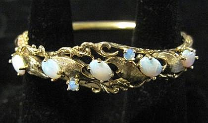 14 karat yellow gold opal bangle bracelet, , Featuring five oval opals and two round opals in foliate motif mounting.