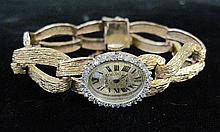 Lady's 14 karat yellow gold and diamond dress watch, , Textured gold tone oval face with Roman numeral dial, petite round cut diamond