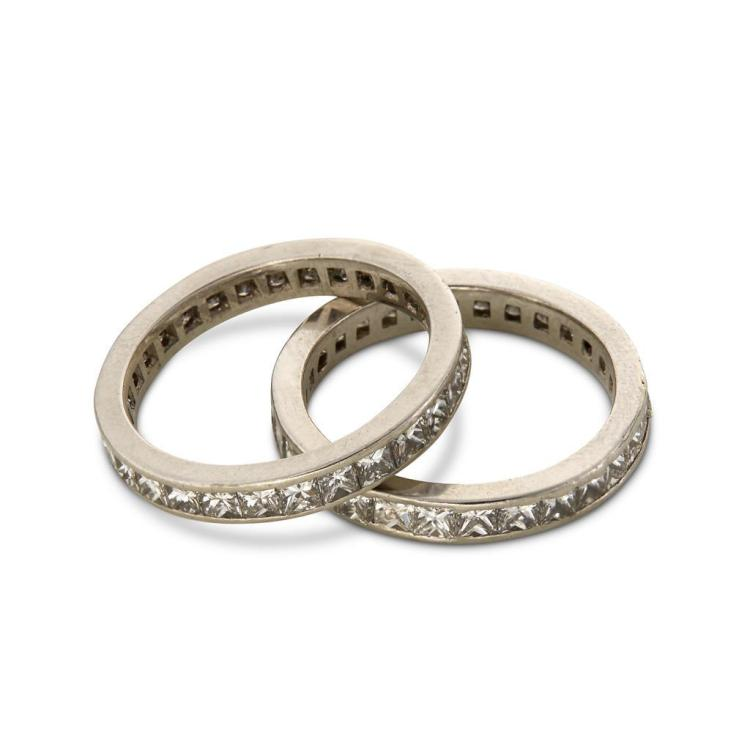 A collection of two matching diamond and platinum eternity bands,
