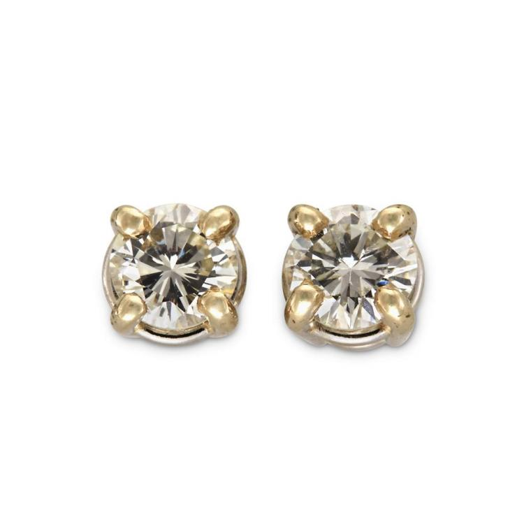 A pair of diamond and fourteen karat white gold earrings,