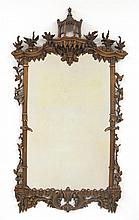 Chippendale style carved and giltwood looking glass, 20th century, The rectangular mirror plate enclosed within a stalactite, C-scroll,