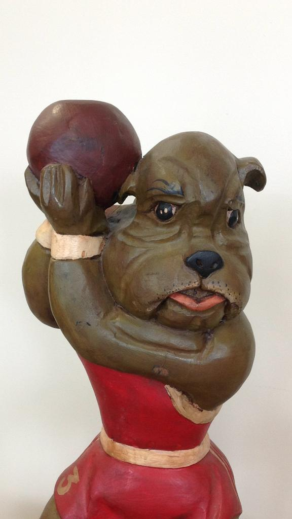 Large wood carved dog sculpture with basketball