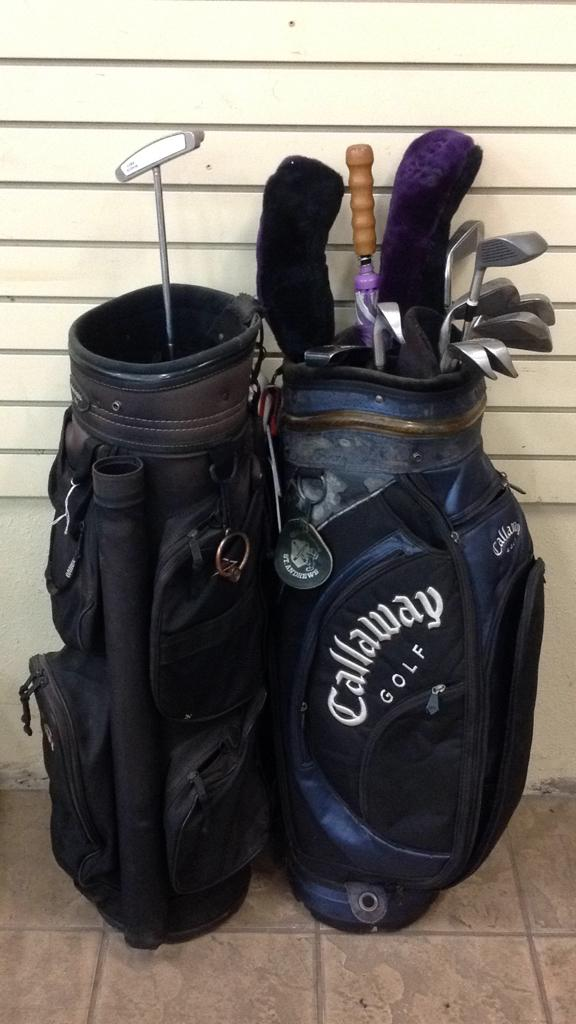 Pair of golf bags and clubs