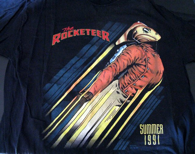 ROCKETEER - LIMITED EDITION TEE SHIRT SDCC - 1991- XL - Black short sleeve tee with an awesome Rocketeer graphic printed on the front. A San Diego Comic Con Exclusive. Worn once at the time, and archived since. Excellent.