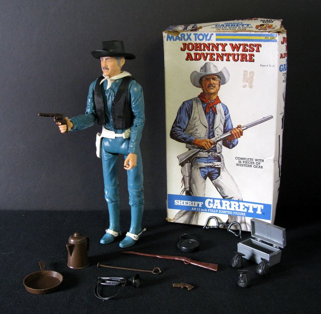 "VINTAGE SHERIFF GARRETT JOHHNY WEST ACTION FIGURE – Marx Toys, 1975 – 11"" tall poseable plastic Sherriff Garrett figure. Complete with multiple accessories and original full-color box. Figure Very Good, box Good."