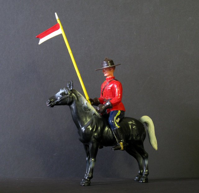 "CANADIAN MOUNTIE & HORSE VINTAGE FIGURINE SET – Early 1960's – Colorful plastic figure of Canadian Mountie on horse. Stands 8"" tall x 8"" long. Complete with removable flag. Very Good."