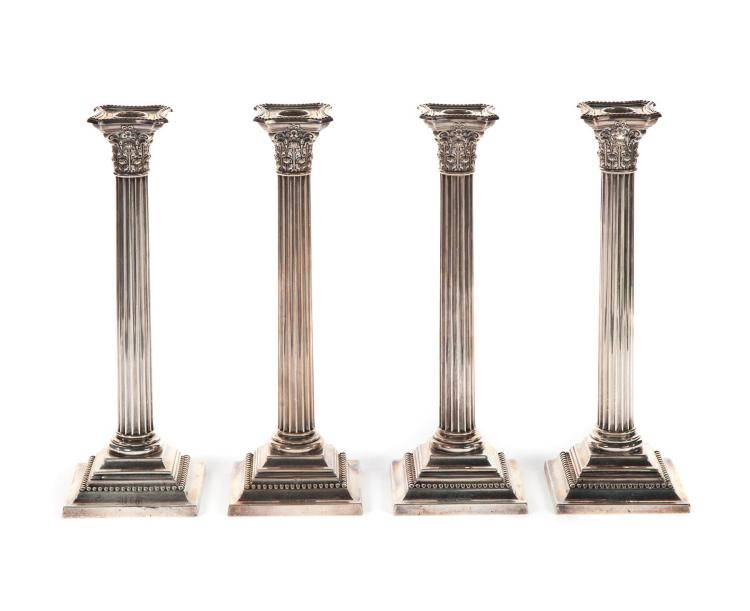 FOUR WEIGHTED STERLING CANDLESTICKS.