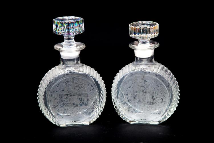 TWO CLEAR GLASS DECANTERS WITH ETCHED DESIGNS.