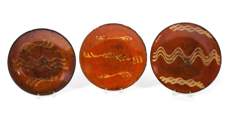 THREE REDWARE PLATES WITH COGGLED RIMS, AND YELLOW SLIP DECORATION.