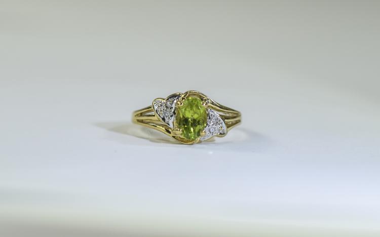 9 Carat Gold Dress Ring central peridot, set betwe