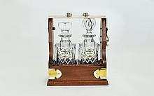 Modern Mahogany & Chrome Mounted Two Bottle Tantalus, Inset With Two Cut Glass Decanters. Measures 11.5'' In Height & 9'' In Width.