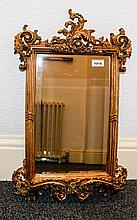 Bevelled Glass Mirror In Ornate Yellow Gilt Frame Small mirror with decorative Rococo yellow gold wood frame and floral scroll moulding and carved detail to top. Approx dimensions 15 x 24 inches