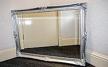 Mantle Mirror Large silver framed bevelled glass mirror with ornate molded decoration to corners. Approx dimensions 40 x 29.5 inches
