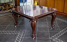 Victorian Dining Table Of Square form with moulded edge. Carved shaped supports on castors. 55 x 47 inches