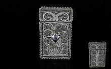 North African White Metal Filigree Card Case, a European style hinged card case, 3.75 inches x 2.25, in allover delicate filigree, probably in a low grade silver, a shield shaped cartouche applied to the front (hinge loose, lacking clasp)