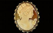A Vintage Nice Quality Oval Shaped Shell Cameo, Depicting a Portrait of a Classical Maiden, within a 9ct Gold Mount. Fully Hallmarked for 9.375. 1.75 Inches High. Broken catch.
