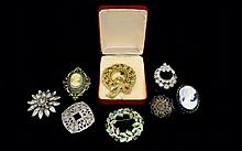 A Collection Of Vintage Costume Jewellery Brooches Eight items in total to include, boxed gold tone Christmas wreath with red and green crystals, two pewter filigree brooches, oval cameo brooch with sage green mount and green crystals. Also, paste