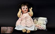 Simon Halbig German 1839 -1943 Bisque Headed Doll with Star of David to the reverse of head, open smiling mouth with teeth, jointed composition body and glass eyes. Together with a collection of dolls clothes.