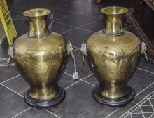 Pair Of Large Brass Vases, With Mask And Ring Handles, Raised On Circular B