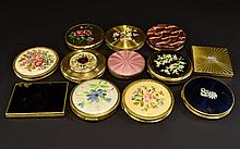 A Large Collection Of Vintage Compacts Twelve in total, each with decorative floral theme to include several gold tone circular compacts with embroidered floral detail to top. Also, two crystal set compacts and various floral motif gold tone designs.