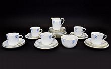 Art Nouveau Design Part Tea Service By New Chelsea Staffordshire Twenty seven pieces in total to include milk jug, cake plates, dinner plates, tea cups etc. White ground with charming blue stylised Art Nouveau trim and gilt accents. Each marked to