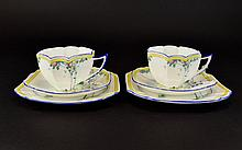 A Pair Of Shelley Art Deco Queen Anne Trios Two in total each comprising charger, saucer and cup, each in yellow, blue, and green stylised tree and butterfly design. Each marked to underside, 'Shelley England, Rd. 723404. Good condition