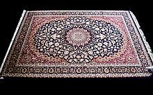 A Large Woven Silk Carpet Keshan rug with beige ground and traditional Middle Eastern floral and foliate border detail with central cruciform pattern in blue, cream, ochre, red and midnight blue. Brand new condition, 2.30 x 1.60M