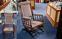Antique Rocking Chair Of Plain form with spindle arm rests, upholstered in dove grey chenille. Height, 41 inches.