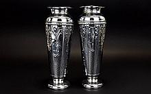 A Pair Of Early 20th Century Beldray Metalware Vases Two trumpet form vases in late nouveau style finished in planished chrome with reeded border and embossed fleur de lys design to sides. Marked Beldray, Made In England to undersides. Some dings to