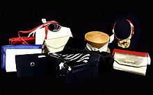 A Large Collection Of Accessories Sixteen items in total to include several envelope clutch bags, silver tone top handle bag, cream faux leather top hanle bag, several 1980's chainmail clutch bags etc. Also three hats to include straw topper with