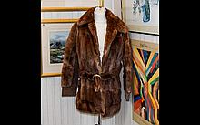 A Ladies Musquash Jacket. A ladies hip length brown jacket with belt and suede cuffs and inserts. Hook and eye fastening, poly satin lining. Approx size 10-12