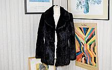 A Ladies Vintage Rabbit Fur Jacket Black Coney jacket with concealed hook and eye closure, revere collar and side seam pockets. Concealed internal pocket, lined in black poly-satin. Pelts in very good condition, approx size, UK 12 -14