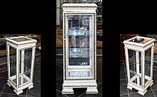 An Ornate Glazed And Mirrored Rectangular Display Cabinet In The French Style. Finished in cream gloss with gilt floral and foliate moulding. Two internal glass shelves, mirrored top and base. Wired for lighting. Height 34 inches, width 12 inches and