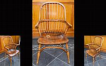 A Yew And Elm wood Windsor Armchair With Dished Seat. Circa 19th Century. Bow shaped strectchers. WOnderful period chair. Seat size 18.25 x 21.25 inches. 39.75 inches in height and 24 inches in width.